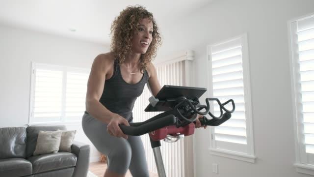 가정에서 스핀을 자전거에 운동 하는 여자 - 운동장비 스톡 비디오 및 b-롤 화면