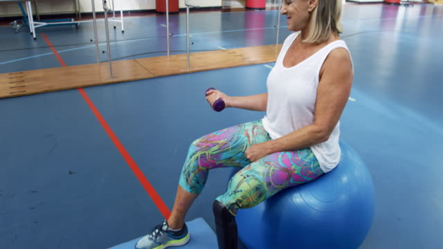 Woman exercising with a prosthetic leg Side view of a Caucasian woman with a prosthetic leg sitting on an exercise ball at a sports centre gym wearing sports clothes and exercising her arm lifting a dumbbell physiology stock videos & royalty-free footage