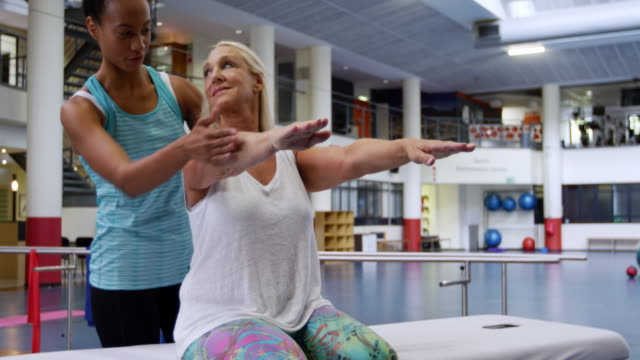Woman exercising with a prosthetic leg Side view of a Caucasian woman with a prosthetic leg sitting on an examination table at a sports centre gym wearing sports clothes, with an African American female physiotherapist helping her to exercise her arms physiology stock videos & royalty-free footage