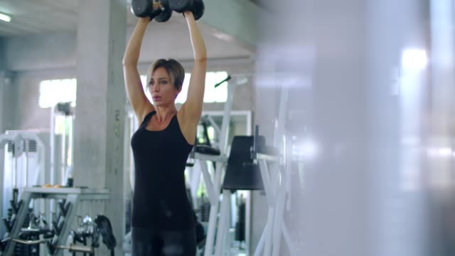 체육관에서 아령 아령으로 운동 하는 여자 - 보디 빌딩 스톡 비디오 및 b-롤 화면