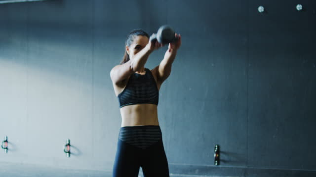 Woman Exercising with Kettlebells Woman working out with kettlebells in the gym cross training stock videos & royalty-free footage