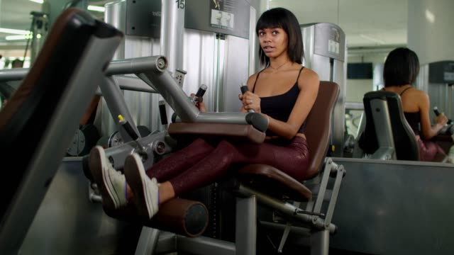 Woman exercising with leg extension machine at gym