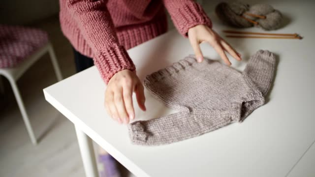 woman expecting baby looking at knitted sweater lying on table. handmade clothes - abbigliamento da neonato video stock e b–roll