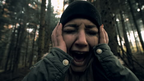 Woman experiencing panic attack in the forest Two camera stabilization shots of a young terrified woman screaming in the forest like she would be lost or having a panic attack. Shot includes original sound. Also available in 4K resolution. fear stock videos & royalty-free footage