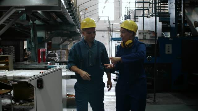 arbeitsprozess, mann zu erklären, frau - bauarbeiterhelm stock-videos und b-roll-filmmaterial