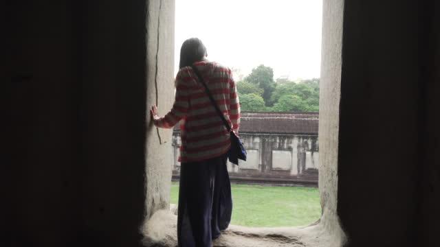 kadın kamboçya'daki antik tapınak araştırıyor - kamboçya stok videoları ve detay görüntü çekimi