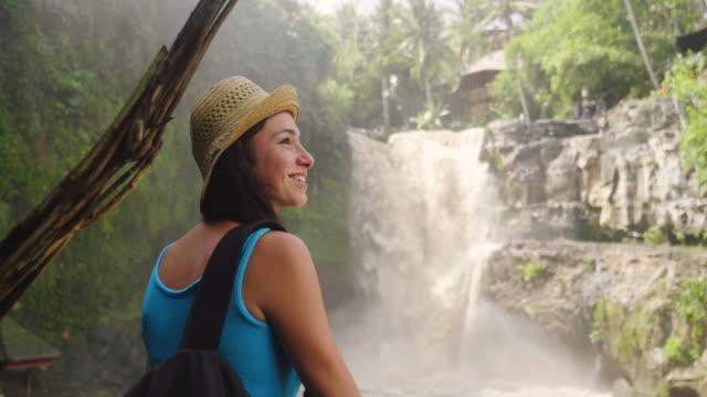 vidéos et rushes de une femme explore de nouveaux endroits magiques et fantastiques à travers le monde est en face d'une cascade, entouré par la nature et la propagation de ses bras pour respirer et se détendre. - prendre un bain