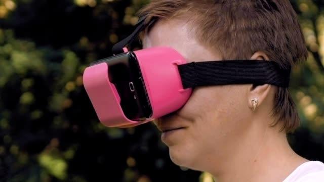 Woman explores virtual reality using VR glasses video