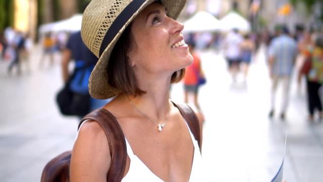 vídeos de stock, filmes e b-roll de mulher de explorar a cidade mapa na mão e olhar ao redor - turista