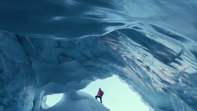 Woman exploring ice cave Woman on a winter trip. Exploring majestic ice cave ice stock videos & royalty-free footage