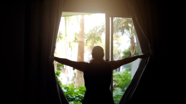 Woman exposing curtains and Looking at the tropical garden in slow motion 180fps