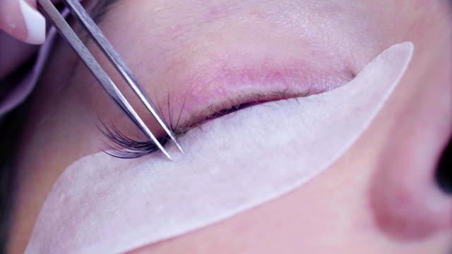 女性の目。サロンでまつげ拡張手順 - まつげ点の映像素材/bロール