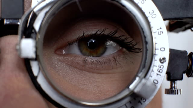 Woman eye with changed lens in phoropter, visual acuity test, cornea diagnostics Woman eye with changed lens in phoropter, visual acuity test, cornea diagnostics eye exam stock videos & royalty-free footage