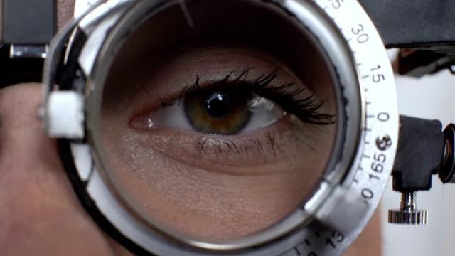 frauenauge mit veränderter linse in phoropter, sehschärfetest, hornhautdiagnostik - sehvermögen stock-videos und b-roll-filmmaterial