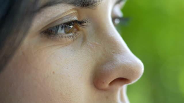 woman eyes side view closeup female looks down sadly accepts broken relationship - cisza filmów i materiałów b-roll