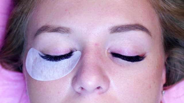 Woman face. Cosmetologist combing eyelashes video