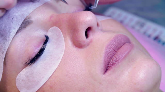 vídeos de stock e filmes b-roll de woman face. eyelash extension procedure in salon - cílio