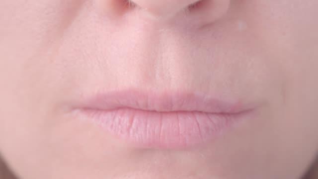 stockvideo's en b-roll-footage met gezicht van de vrouw met de vinger in de buurt van lips - conceptuele video gebaar rustigere, maken hush (shh) gebaar macro video - stilte