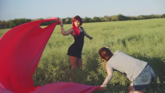 stockvideo's en b-roll-footage met vrouw fashion fotograaf fotograferen op de camera een stijlvolle jonge vrouw model met rood haar en tatoeages - roze haar