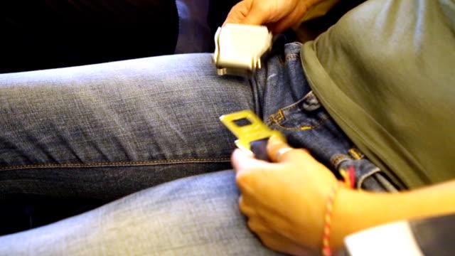 a woman fasten his seat belt on an airplane - mebel do siedzenia filmów i materiałów b-roll