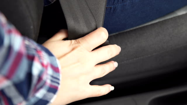 A woman fastens her seat belt in the car video