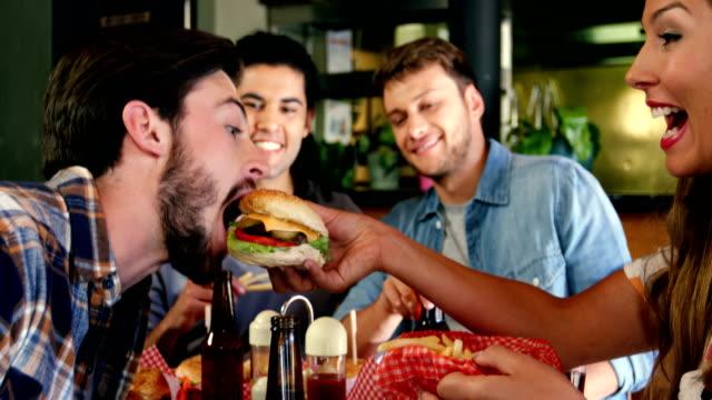 vídeos y material grabado en eventos de stock de mujer alimentación burger man - hamburguesa