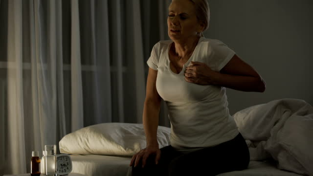 Woman feeling sharp pain in her chest, suffering heart attack at night, health video