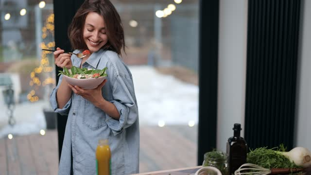 Woman feeling well with healthy food at home Beautiful young woman eating healthy salad at cozy living room near the window at home, dancing and feeling easy. Healthy veggie food and wellness concept carefree stock videos & royalty-free footage