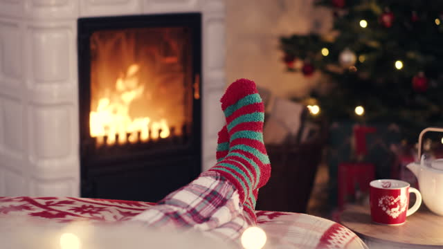 vídeos de stock e filmes b-roll de woman feet in cozy christmas woolen socks near fireplace with decorated xmas tree and tee cup in background - lareira