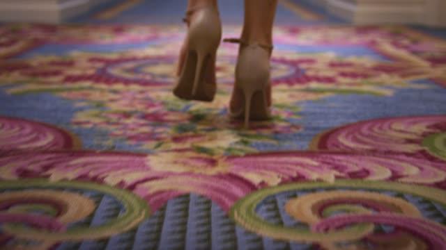 vídeos de stock, filmes e b-roll de vista traseira de pés de mulher em sapatos de salto alto andando no chão de carpete - salto alto