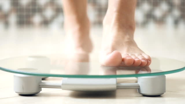 woman feet standing on electronic scales for weight control  on the bathroom.   close-up . - stare in piedi video stock e b–roll