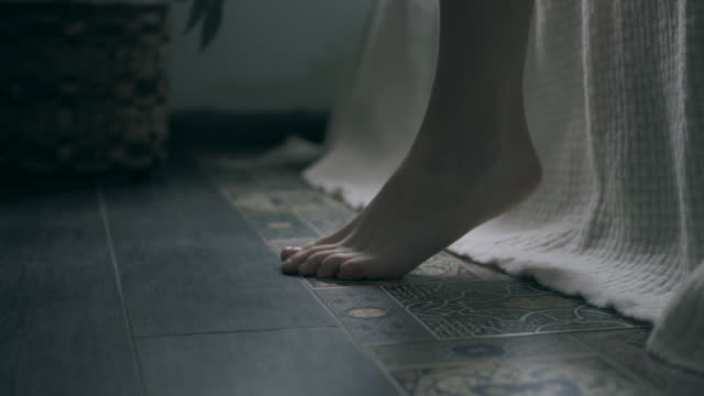 woman feet touching floor in the morning - bed filmów i materiałów b-roll