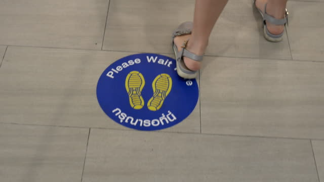 POV , Woman feet walking in shopping mall , COVID-19 business signage on floor , new normal concept - vídeo