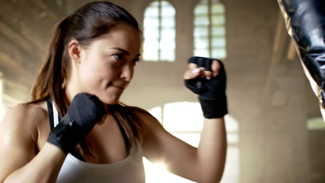 woman fighter training with punching bag that her partner holds. she's athletic and has powerful punch. - sacco per il pugilato video stock e b–roll