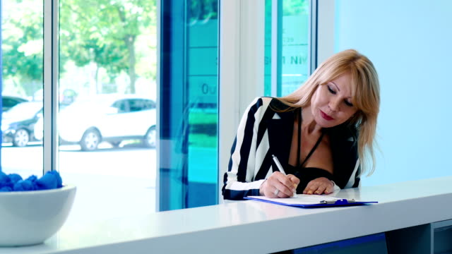 Frau füllt Formular an der Rezeption in Klinik – Video