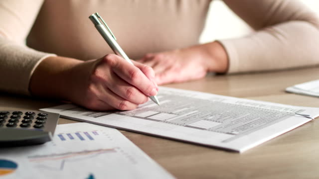 Woman filling and signing tax form Woman filling and signing tax form at desk, 4K video. form filling stock videos & royalty-free footage