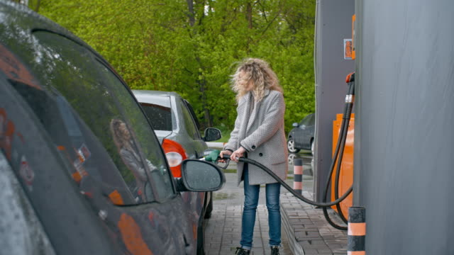 Woman Filling Full Tank at Gas Station Woman filling car at gas pump and then putting back fueling nozzle and sitting into her automobile refueling stock videos & royalty-free footage