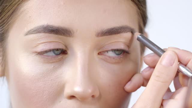 vídeos de stock e filmes b-roll de woman filling in eyebrows - sobrancelha