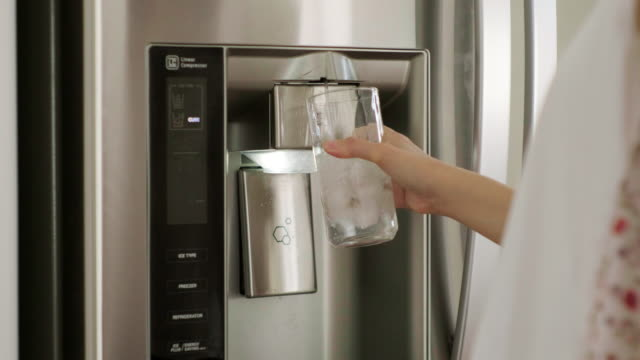 Woman Filling Water Cup From Home Refrigerator A women filling a glass with ice and water from a home kitchen refrigerator. fridge stock videos & royalty-free footage