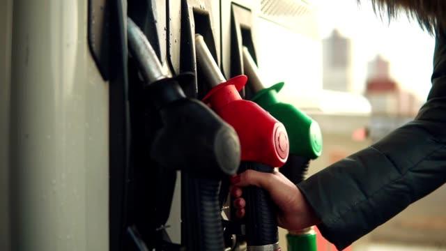 Woman fills gasoline car. Hand close up