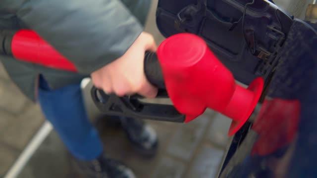 woman fills gasoline car. hand close up - заправляться стоковые видео и кадры b-roll