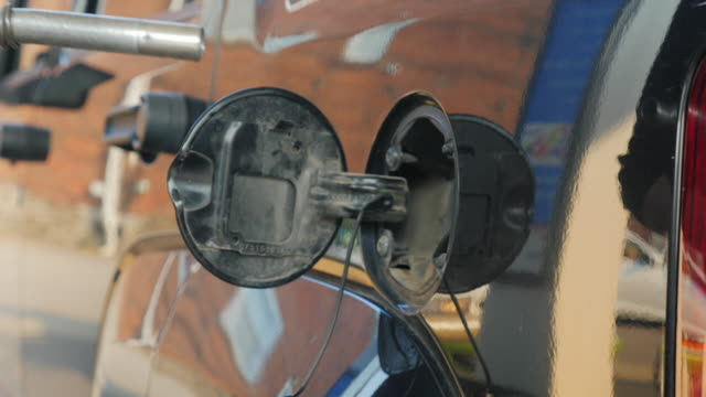 A woman fills petrol your car. In the frame are only visible hands and opening the gas tank video