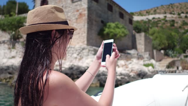 Woman filming and taking some pictures at boat travel in Hvar Croatia