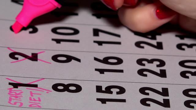 kvinnan fingrar med rosa markör korsning dagar på kalendern. start av kost koncept - calendar workout bildbanksvideor och videomaterial från bakom kulisserna