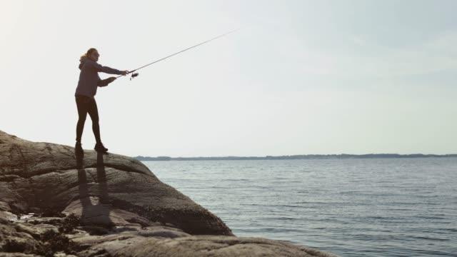 Frau fischt mit einer Rute von einem Felsvorsprung – Video