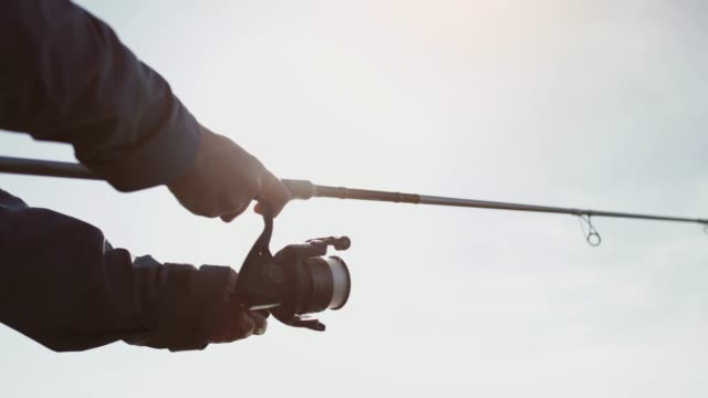 woman fishing with a rod from a rock spot - spranga video stock e b–roll