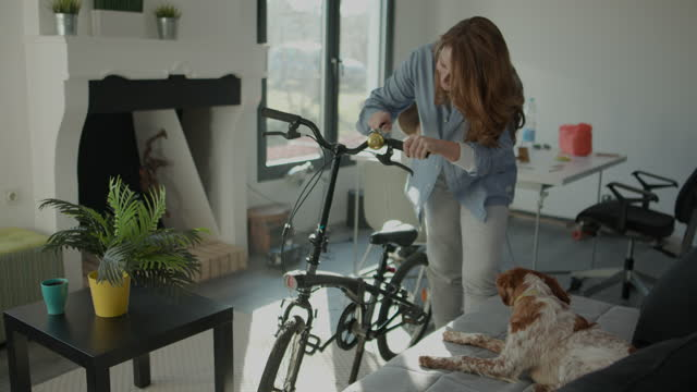 Woman fixing a bicycle bell at living room