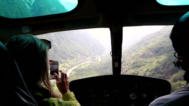 woman flies in helicopter alongside pilot, takes pictures - luna park video stock e b–roll