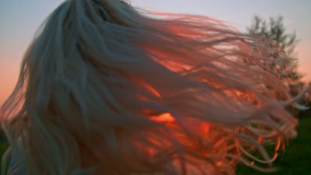 SLO MO Woman flipping her hair Super slow motion close up shot of an unrecognizable woman flipping her hair somewhere in the countryside at sunset. one mid adult woman only stock videos & royalty-free footage