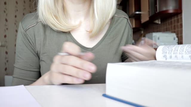 frau blättert durch das große buch, wörterbuch und schreibt einige informationen aus, macht notizen, bildung und studentenkonzept aus nächster nähe - nachhilfelehrer stock-videos und b-roll-filmmaterial